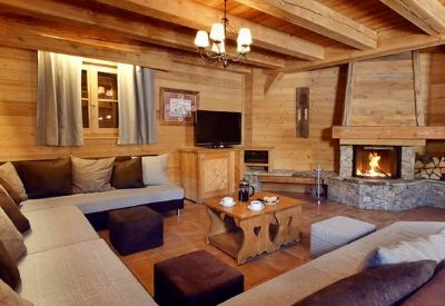 A large living room with comfortable sofas and a fire in ski chalet La Chapelle