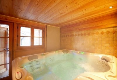 A steaming indoor hot tub in ski Chalet La Maison