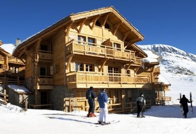 People skiing on a piste past Chalet Le Manoir in Alpe d'Huez