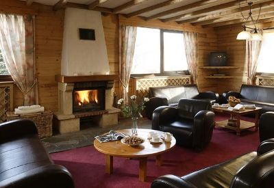 A comfotable living room with leather sofas and an open fire in ski Chalet Les Eterlous