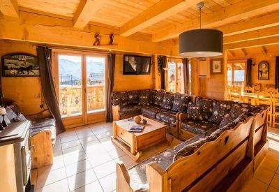 An open plan dinning room and living room with a wood burner in Chalet Louisa