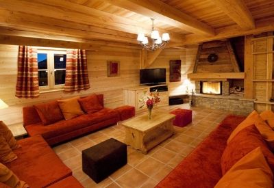A large living room with comfortable sofas and a fire in Club Chateau in Alpe d'Huez