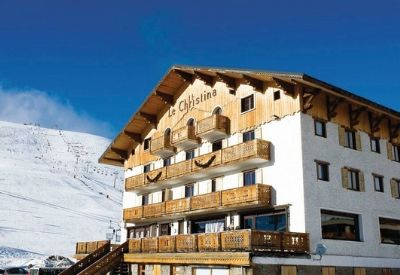 The outside of Hotel Le Christina in Alpe d'Huez with a snow covered piste in the background