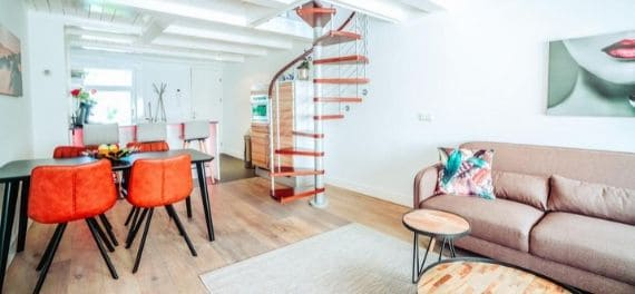 An apartment with a pink sofa and a spiral staircase