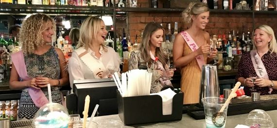 Women on a hen do behind a cocktail bar