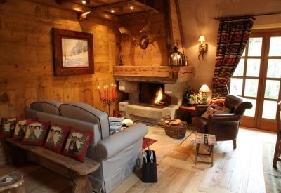 A cosy seating area with leather arm chairs and an open fire at Au Coeur du Neiges