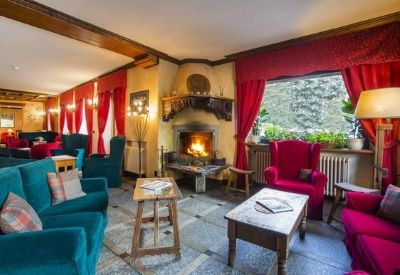 A seating area with sofas and a lit open fire at the Hotel Courmayeur