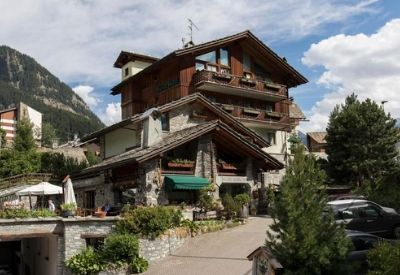 The exterior of the traditional looking Hotel Walser with mountains in the background