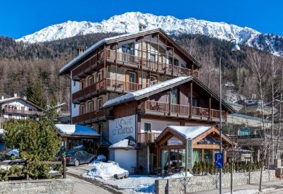 The outside of the Lo Scoiattolo hotel in Courmayeur with snow covered mountains in the background