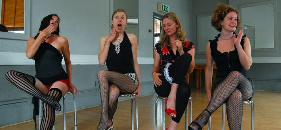 Four women in stockings on chairs in a studio
