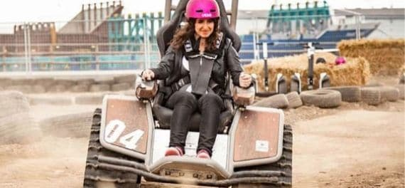 A woman in a pink helmet on an off road elctro chair