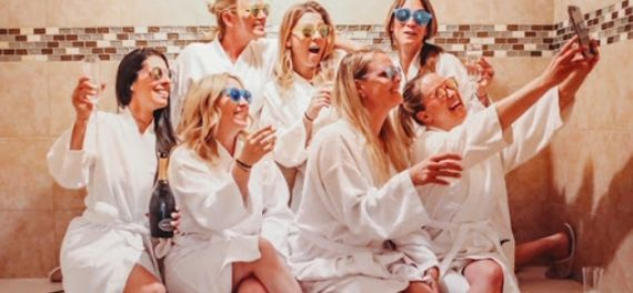 A group of women in dressing gowns taking a selfie in a spa