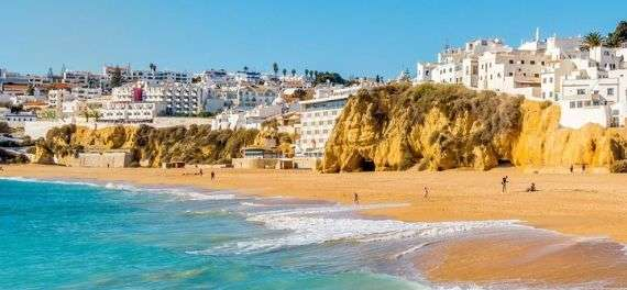 The beach and cliffs in Albufeira with buildings in the background