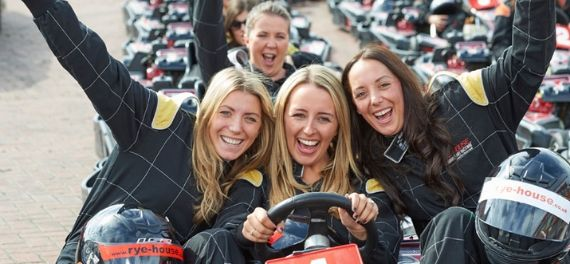 Four women in overalls sitting on go karts