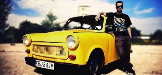 A man standing next to a yellow soviet-style car