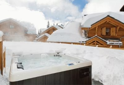 A steaming outdoor hot tub with mountains in the background at Chalet Favero