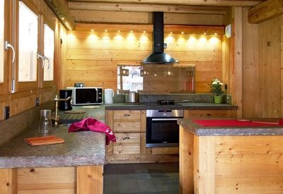A modern wood clad kitchen in self catered Chalet Le Loup Lodge