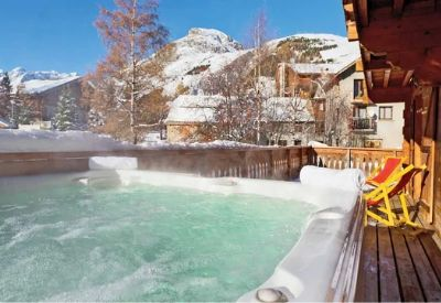 A steaming outdoor hot tub with mountains in the background at Chalet L'Icheve