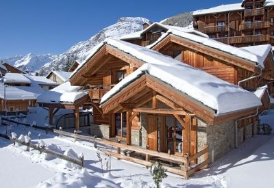 The outside of a traditional ski chalet in the snow with mountains in the background
