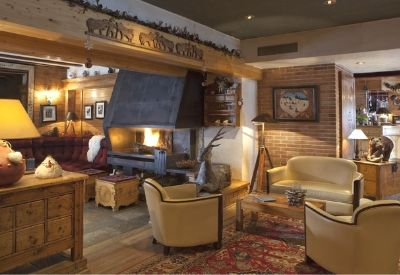 The lounge area with comfortable seating and an open fire at Hotel Les Melezes