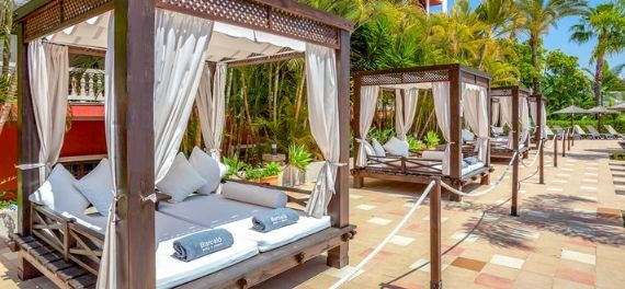 Cabana beds by a swimming pool on a sunny day