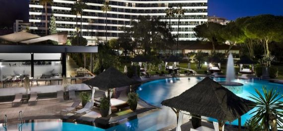 A posh hotel with twoi swimming pools lit up at night