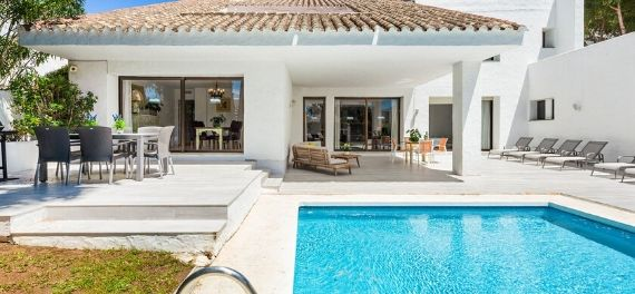 a single story white holiday villa with a swimming pool