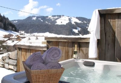 An outdoor hot tub in front of snow covered mountains