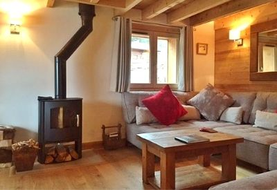 A wood burning stove and sofas in Chalet Mimi