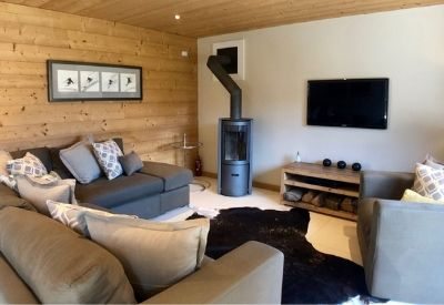 Sofas and a TV next to a wood burning stove in Chalet Pruger
