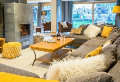 A high end ski chalet living room with large sofas and a fire