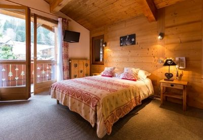 A double bedroom with wooden walls in Hotel Igloo with mountain views