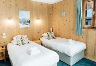 A wood clad hotel room with twin beds in Hotel L'Aubergade