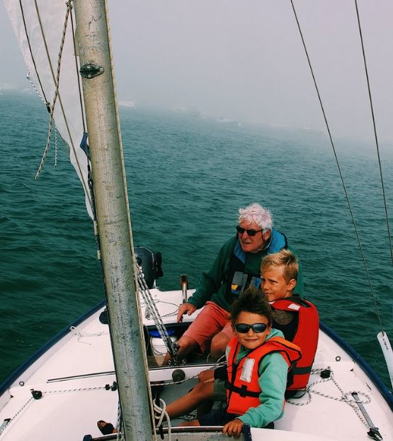 A granfather and two boys on a small sailing boat
