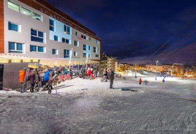 The Aparthotel Les Olimpiades lit up at night next to a ski piste