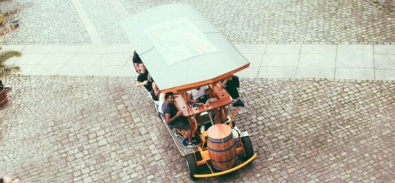 A beer bike cycling on a cobble Street in Budapest