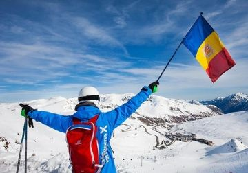 a man in ski clothes with an Andorran flag and snow covered mountains