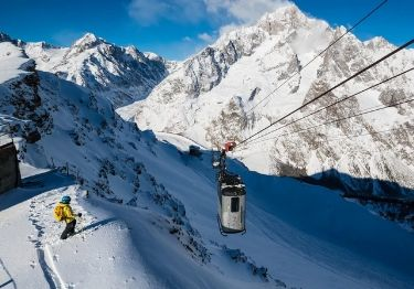 a skier next to a small ski lift high up on a mountain