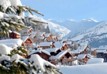 Snow covered chalets in Meribel with trees in the foreground