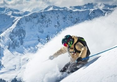 A skier skiing steep powder with large mountains in the background