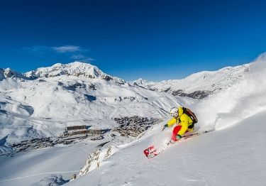 A skier in a bright yellow coat sking with Tignes in the background