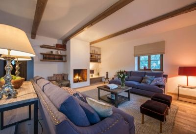 Large sofas around a lit fire in a room with wooden beams