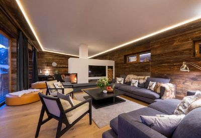 A luxury ski chalet's living room with an open fire and comfortable sofas