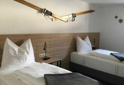 A twin hotel room with wooden skis on the wall