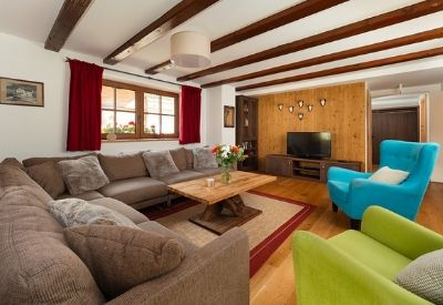 A high end ski chalet's living room with sofas and two arm chairs