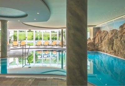 A large indoor swimming pool with marble pillars