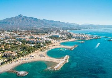 The beach in Marbella with the city and hills in the background