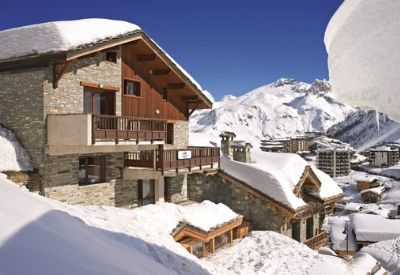 The outside of a large snow covered ski chalet