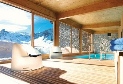A small swimming pool in a room with large windows and snow covered mountains outside