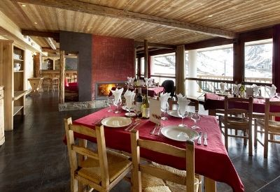 The dining room in a large ski chalet with full length windows and mountain views